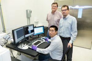 Yang Song da ORNL (sentada), Dale Hensley (de pé à esquerda) e Adam Rondinone examinam uma amostra de nanospike de carbono com um microscópio eletrônico de varredura.
